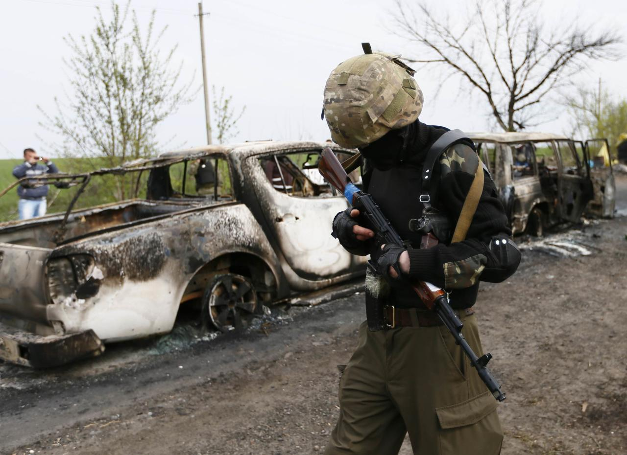 A Pro-Russian militant walks past burnt cars near a checkpoint that was the scene of a gunfight overnight near the city of Slaviansk, April 20, 2014. At least two people were killed in a gunfight early on Sunday near a Ukrainian city controlled by pro-Russian separatists, testing an already fragile international accord that is supposed to defuse Ukraine's armed stand-off. REUTERS/Gleb Garanich (UKRAINE - Tags: POLITICS MILITARY CIVIL UNREST CRIME LAW TPX IMAGES OF THE DAY)