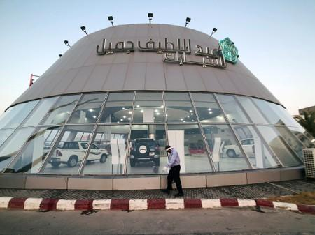 A worker cleans the front face of the car showroom of Abdul Latif Jamil Automobile, Saudi dealer for Toyota in Dhahran