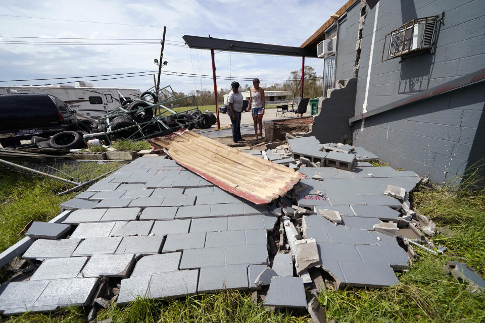 Monique Benjamin, left, and her daughter Amiah Winbush, 17, look at the damage to their car detailing business, in Lake Charles, La., in the aftermath of Hurricane Laura, Sunday, Aug. 30, 2020. (AP Photo/Gerald Herbert)