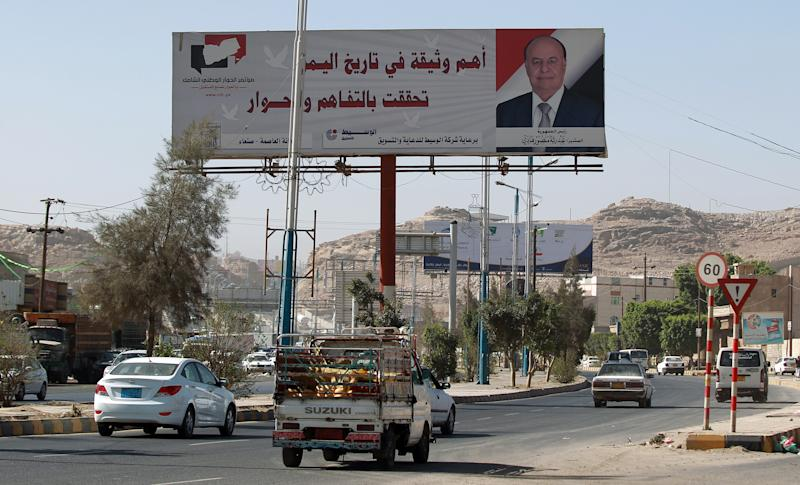 Motorists drive past a giant billboard bearing a portrait of President Abedrabbo Mansour Hadi on February 22, 2015 in the Yemeni capital of Sanaa (AFP Photo/Mohammed Huwais)