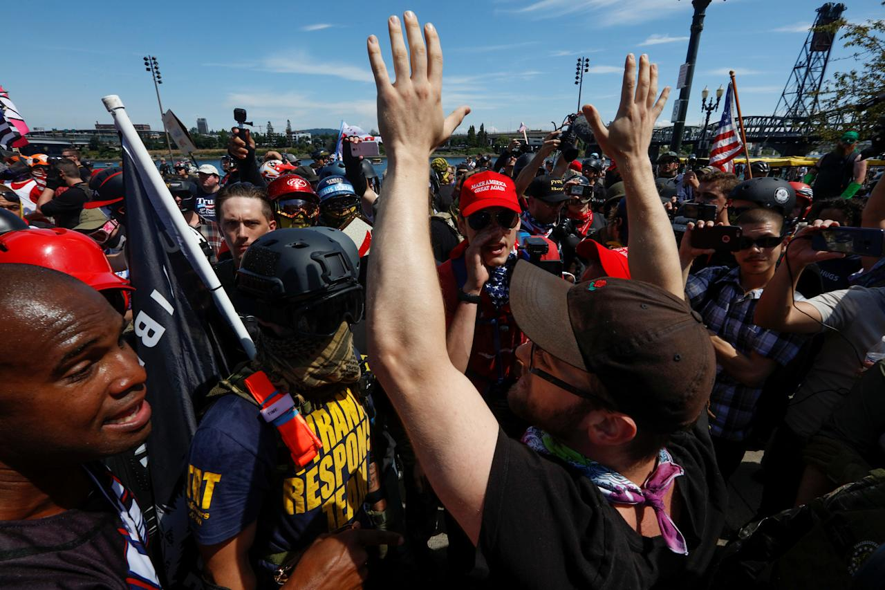 <p>A counterprotester raises his arms as he talks with supporters of the Patriot Prayer group during a rally in Portland, Ore., Aug. 4, 2018. (Photo: Bob Strong/Reuters) </p>