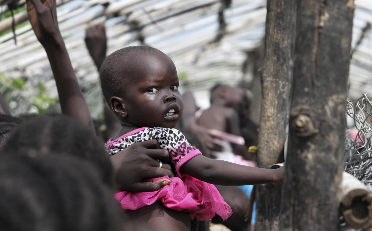 In this photo taken Monday, July 25, 2016, a baby is lifted up as people queue for food distribution in a camp for the displaced at the United Nations base in Juba, South Sudan. When South Sudan's president signed a peace deal a year ago to end the country's civil war he added 16 reservations to the agreement, which have now become a map of how it has unraveled. (AP Photo/Justin Lynch)