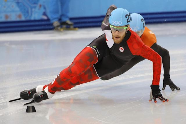 Olivier Jean of Canada, front, and Sjinkie Knegt of Netherlands compete in a men's 1000m short track speedskating heat at the Iceberg Skating Palace during the 2014 Winter Olympics, Thursday, Feb. 13, 2014, in Sochi, Russia. (AP Photo/Vadim Ghirda)