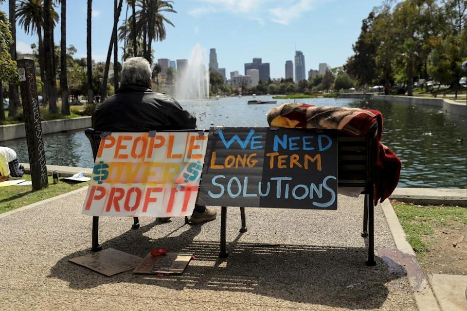 A homeless man sits on a bench adorned with protest signs at Echo Park Lake.