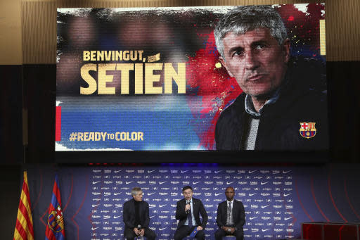 Quique Setien, left, joins FC Barcelona's President Josep Maria Bartomeu, center, and director of football Eric Abidal, right, in a news conference after being officially introduced as the new soccer coach of FC Barcelona at the Camp Nou stadium in Barcelona, Spain, Tuesday, Jan. 14, 2020. Barcelona made a rare coaching change midway through the season, replacing Ernesto Valverde with former Real Betis manager Quique Setien on Monday. (AP Photo/Emilio Morenatti)