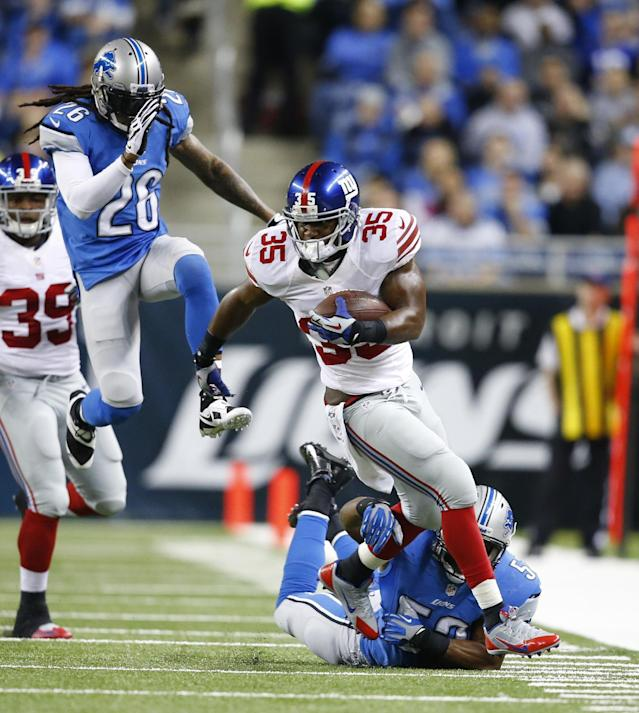 New York Giants running back Andre Brown (35) is chased by Detroit Lions linebacker Rocky McIntosh, bottom, and free safety Louis Delmas (26) during the first quarter of an NFL football game, Sunday, Dec. 22, 2013, in Detroit. (AP Photo/Rick Osentoski)