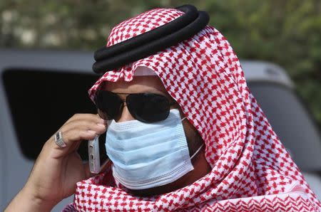 A man with mask speaks on his mobile phone in Jeddah May 29, 2014. Saudi Arabia is working with international scientific organisations to improve its response to a deadly new virus that has killed 186 people in the kingdom, its acting health minister Adel Fakieh told Reuters on Wednesday. REUTERS/Mohamed Alhwaity