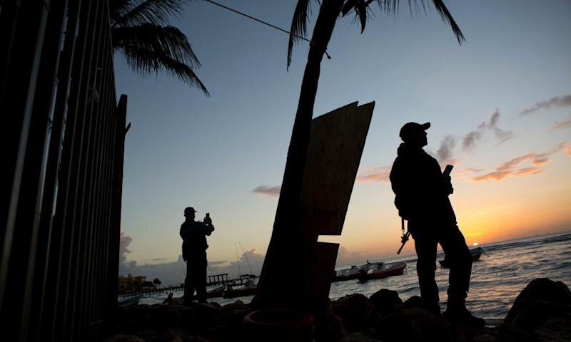 Municipal police watch the sunrise as they stand guard on the beach in front of the Blue Parrot club, a day after a deadly early morning shooting, in Playa del Carmen, just south of Cancún.