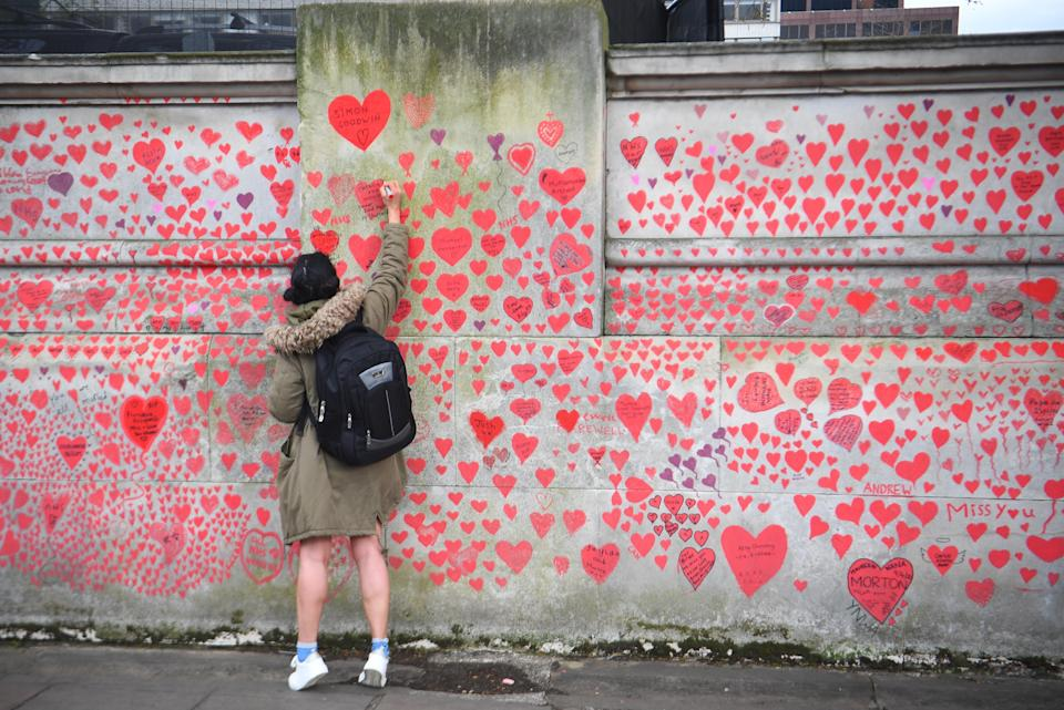 A woman writes in a heart on the National Covid Memorial Wall on the Embankment in London (Victoria Jones/PA) (PA Wire)