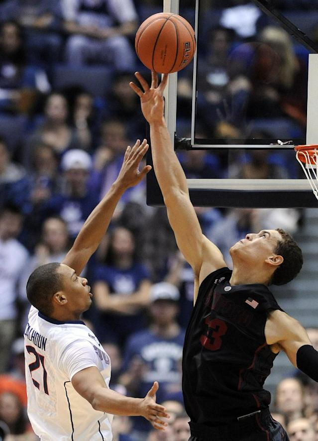 Stanford's Dwight Powell (33) blocks the shot of Connecticut's Omar Calhoun (21) during the first half of an NCAA college basketball game in Hartford, Conn., Wednesday, Dec. 18, 2013. (AP Photo/Fred Beckham)