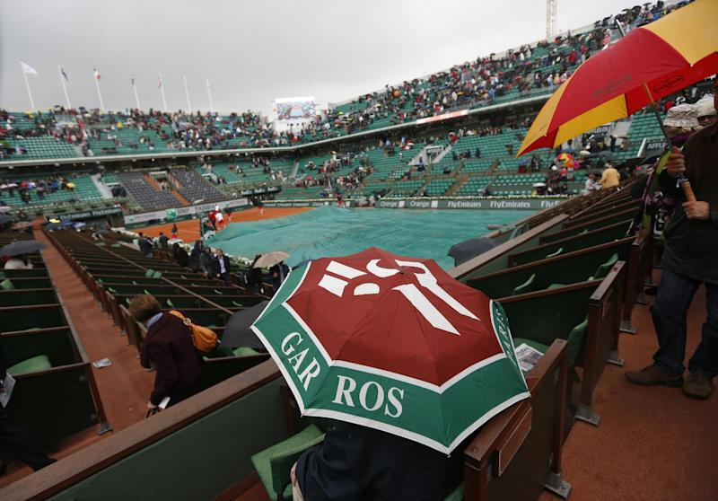 Spectators take cover under umbrellas as rain interrupts matches at the French Open tennis tournament, at Roland Garros stadium in Paris, Thursday, May 30, 2013. (AP Photo/Petr David Josek)