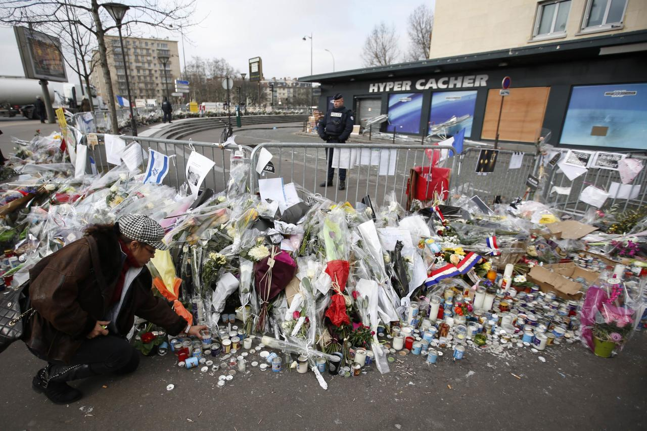 A woman lights candles in front of the Hyper Cacher kosher supermarket at the Porte de Vincennes in Paris January 21, 2015. Four people were killed in a hostage-taking situation during an attack by an Islamist militant on January 9. REUTERS/Charles Platiau (FRANCE - Tags: CRIME LAW)