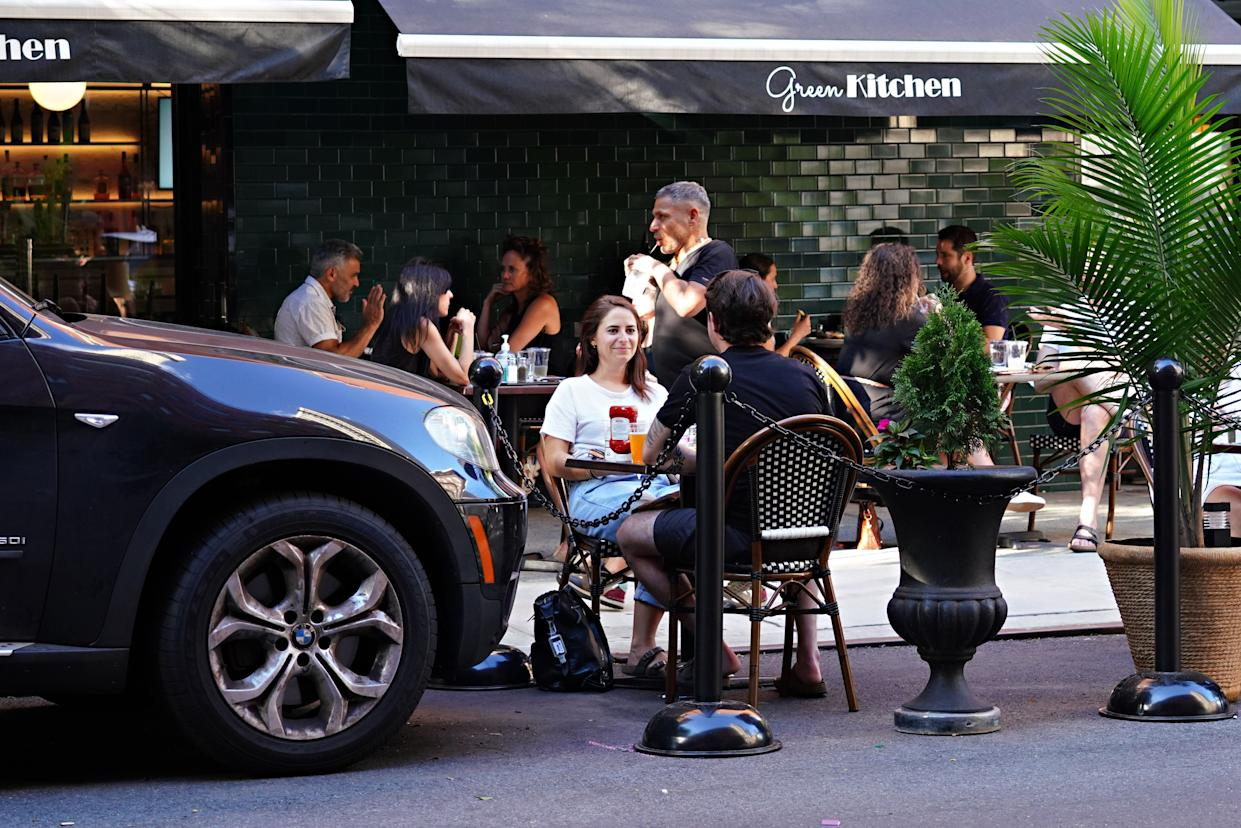 Customers at Green Kitchen in Manhattan are served at outside tables as the city moves into Phase 2 of re-opening following restrictions imposed to curb the coronavirus pandemic on June 24, 2020. Phase 2 permits the reopening of offices, in-store retail, outdoor dining, barbers and beauty parlors and numerous other businesses and is the second of four-phased stages designated by the state.