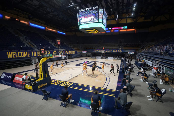 Players and coaches sit apart on the sideline to maintain social distance during the first half of an NCAA college basketball game between California and Arizona State in Berkeley, Calif., Thursday, Dec. 3, 2020. (AP Photo/Jeff Chiu)