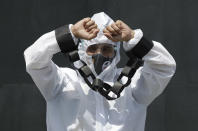 A protester dressed in a protective suit with hands tied with mock chains hold a rally against the G7 summit outside the British Embassy in Taguig, Philippines on Friday, June 11, 2021. The group called on G7 Summit member nations for debt cancellation for poor countries facing difficulties due to the COVID-19 pandemic. (AP Photo/Aaron Favila)