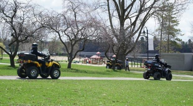 Police officers ride ATVs while patrolling Mooney's Bay park in Ottawa on April 17, 2021, during the COVID-19 pandemic.