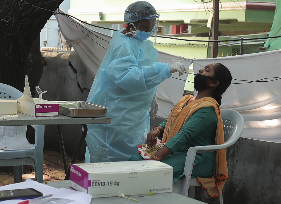 A health worker takes a nasal swab sample at a COVID-19 testing center in Hyderabad, India, Tuesday, Oct. 27, 2020. India reports 36,470 new coronavirus cases, the lowest in more than three months in a continuing downward trend. However, the overall tally neared 8 million, the second in the world behind the U.S. with over 8.7 million positive cases. (AP Photo/Mahesh Kumar A.)