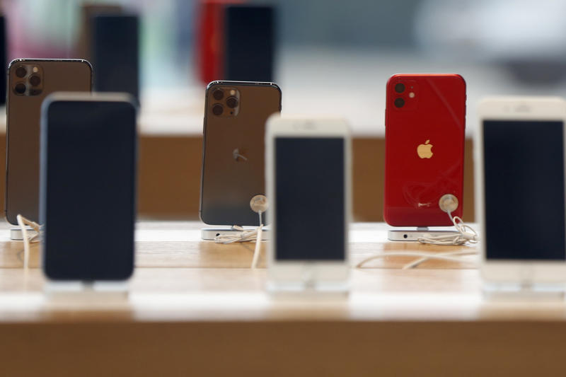 Rows of iPhones are displayed Saturday, March 14, 2020, inside a closed Apple store in downtown Brooklyn in New York. Apple CEO Tim Cook announced the tech giant would close all Apple retail stores outside of China to help stem the global spread of the coronavirus. (AP Photo/Kathy Willens)
