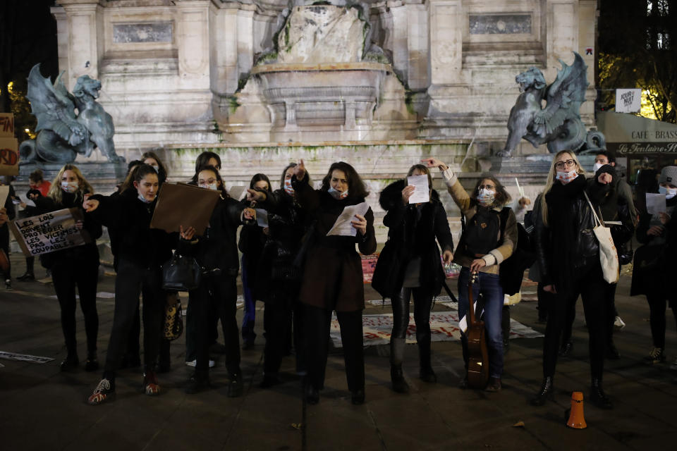 Women gather at the Saint Michel fountain Wednesday, Nov. 25, 2020 in Paris. With domestic violence on the rise amid the pandemic, activists are holding protests Wednesday from France to Turkey and world dignitaries are trying to find ways to protect millions of women killed or abused every year by their partners. (AP Photo/Francois Mori)