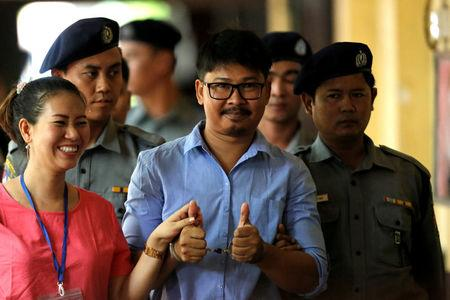 Detained Reuters journalist Wa Lone gives a 'two-thumbs-up' as he arrives with his wife Pan Ei Mon, escorted by police, before a court hearing in Yangon, Myanmar May 22, 2018. REUTERS/Ann Wang