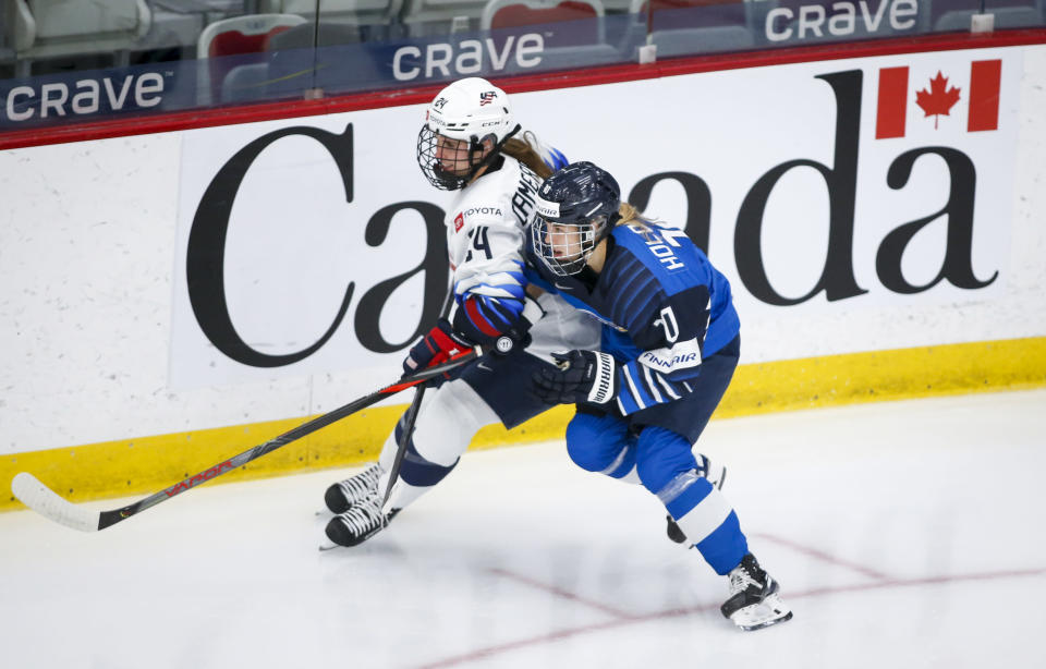 Finland's Elisa Holopainen, right, checks Dani Cameranesi, of the United States, during the first period of an IIHF women's hockey championships semifinal in Calgary, Alberta, Monday, Aug. 30, 2021. (Jeff McIntosh/The Canadian Press via AP)