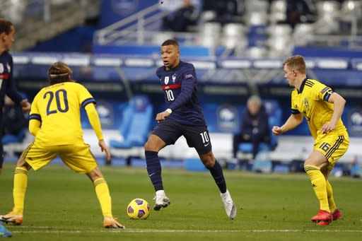 France's Kylian Mbappe, center, controls the ball as Sweden's Emil Krafth, right, and Kristoffer Olsson defend during the UEFA Nations League soccer match between France and Sweden at the Stade de France stadium in Saint-Denis, northern Paris, Tuesday, Nov. 17, 2020. (AP Photo/Francois Mori)