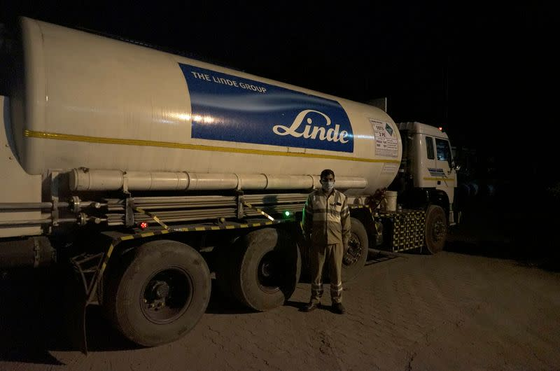 Subhas Kumar Yadav poses in front of a tanker carrying liquid oxygen along a road in Selaqui