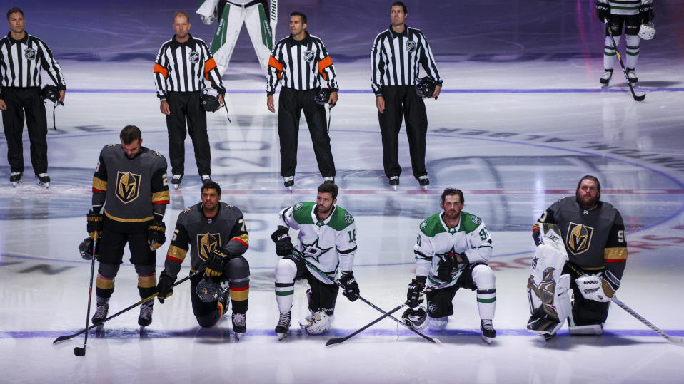EDMONTON, ALBERTA - AUGUST 03:  Ryan Reaves #75 and Robin Lehner #90 of the Vegas Golden Knights kneel during the singing of the American national anthem alongside Jason Dickinson #18 and Tyler Seguin #91 of the Dallas Stars before the start of the Round Robin game during the 2020 NHL Stanley Cup Playoff at Rogers Place on August 03, 2020 in Edmonton, Alberta. (Photo by Dave Sandford/NHLI via Getty Images)