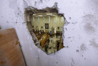 Israeli security forces inspect a damaged synagogue after it was hit by a rocket fired from the Gaza Strip, in Ashkelon, Israel, Sunday, May 16, 2021. (AP Photo/Tsafrir Abayov)