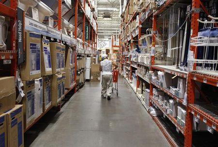 A man pushes his shopping cart down an aisle at a Home Depot store in New York