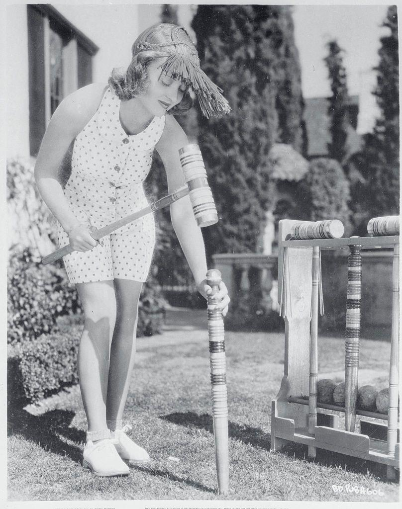 <p>The film star, who was a reported champion croquet player, sets up a croquet course on the lawn of her Hollywood home.</p>