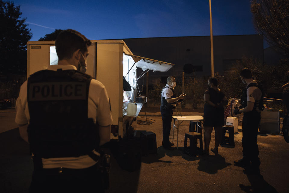 Police major Nicolas, center, talks to a street vendor to check authorizations in the Paris suburb of Garges-les-Gonesse, Tuesday, June, 15, 2021. He is a veteran patrolman in the Paris suburb of Sarcelles and its surrounding towns that are hotspots for crime. He is among the officers who say violence is getting worse. (AP Photo/Lewis Joly)