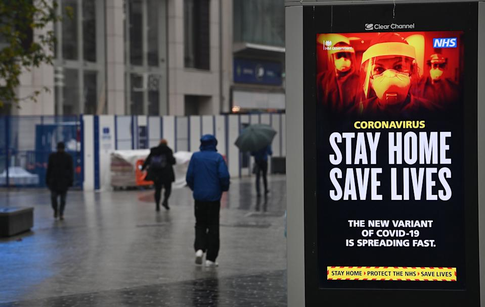 Pedestrians walk past COVID-19 information boards in Liverpool, on January 13, 2021, as non-essential retailers keep their shops closed, due to England's third lockdown. - Britain's interior minister on Tuesday warned that anyone flouting coronavirus lockdown rules would face action from the police, as the government vowed to step up enforcement measures to cut surging infection rates that risk overwhelming health services. (Photo by Paul ELLIS / AFP) (Photo by PAUL ELLIS/AFP via Getty Images)