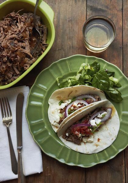 This December 2016 photo shows barbacoa beef tacos in New York. This dish is from a recipe by Katie Workman. (Mia via AP)