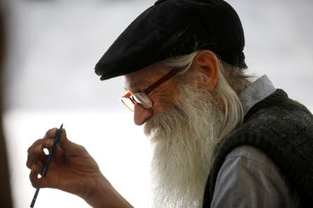 Michael Netzer, an American comics artist formerly named Mike Nasser, sketches a passerby on a bench in Jerusalem