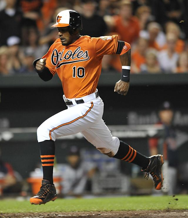 Baltimore Orioles' Adam Jones scores the go ahead run on a sacrifice fly by Chris Davis against the Minnesota Twins in the seventh inning of a baseball game, Saturday, Aug. 30, 2014, in Baltimore. The Orioles won 3-2.(AP Photo/Gail Burton)