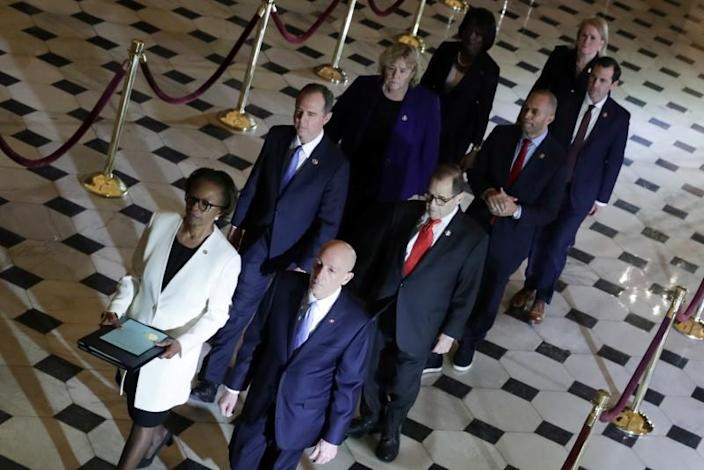U.S. House of Representatives Clerk Johnson and House Sergeant at Arms Irving carry two articles of impeachment against U.S. President Donald Trump during a procession with the seven House trial managers to the Senate in the U.S. Capitol in Washington