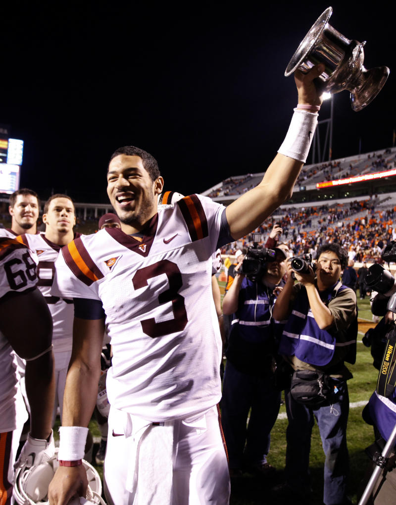 Virginia Tech quarterback Logan Thomas (3) hoists the Commonwealth Cup after they beat Virginia 38-0 in an NCAA college football game at Scott Stadium in Charlottesville, Va., Saturday, Nov. 26, 2011.  (AP Photo/Steve Helber)