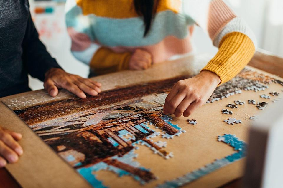 """<p>Doing puzzles can actually help <a href=""""https://www.sciencedaily.com/releases/2019/05/190516082349.htm#:~:text=From%20their%20results%2C%20researchers%20calculate,tests%20measuring%20short%20term%20memory."""" rel=""""nofollow noopener"""" target=""""_blank"""" data-ylk=""""slk:fight brain aging"""" class=""""link rapid-noclick-resp"""">fight brain aging</a>, not to mention make the hours slip by. Sit down with the whole crew to spend some time puzzling, or set one up on the coffee table to keep going over days or weeks. </p><p><strong>RELATED: </strong><a href=""""https://www.goodhousekeeping.com/life/g22664296/best-jigsaw-puzzles/"""" rel=""""nofollow noopener"""" target=""""_blank"""" data-ylk=""""slk:14 of the Absolute Best Puzzles, According to Jigsaw Enthusiasts"""" class=""""link rapid-noclick-resp"""">14 of the Absolute Best Puzzles, According to Jigsaw Enthusiasts</a></p>"""