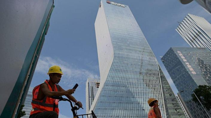 Workers walk in front of the Evergrande headquarters in Shenzhen, southeastern China on September 26, 2021.
