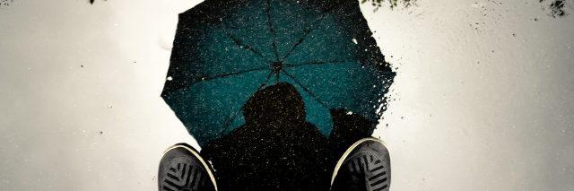A reflection in a puddle of a person standing with an umbrella open and above their head.