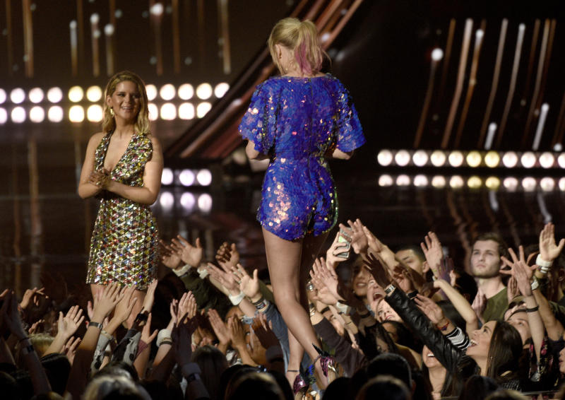 Maren Morris, left, presents Taylor Swift with the award for tour of the year at the iHeartRadio Music Awards. (Chris Pizzello/Invision/AP)