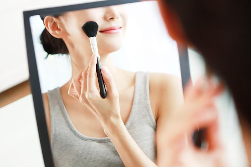 Stock image of a woman applying blusher in front of a mirror. (PHOTO: Getty Images)