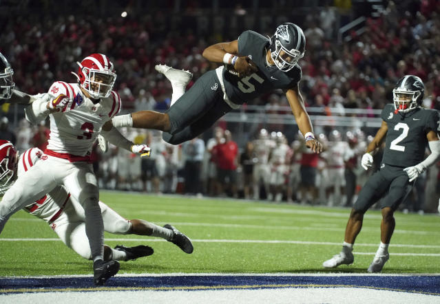 FILE - In this Friday, Oct. 25, 2019 file photo, Despite the acrobatic jump by St. John Bosco quarterback DJ Uiagalelei (5) into the end zone, it was called back due to a penalty against Mater Dei in Bellflower, Calif. Only Texas and Florida produce more major college football players than California, but across the state overall participation in the sport at the high school level is on the decline. The percentage of players competing at the highest level of college football who are from California has dropped, too. (Scott Varley/The Orange County Register via AP, File)