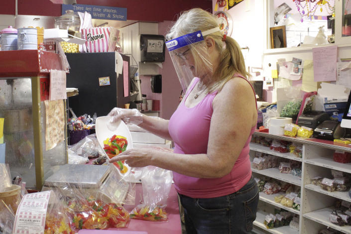 In this Thursday, May 28, 2020, photo, Susan Truax, owner of Bruce's Candy Kitchen, wears a protective plastic face shield while putting candy into a bag in Cannon Beach, Ore. With summer looming, Cannon Beach and thousands of other small, tourist-dependent towns nationwide are struggling to balance fears of contagion with their economic survival in what could be a make-or-break summer. (AP Photo/Gillian Flaccus)