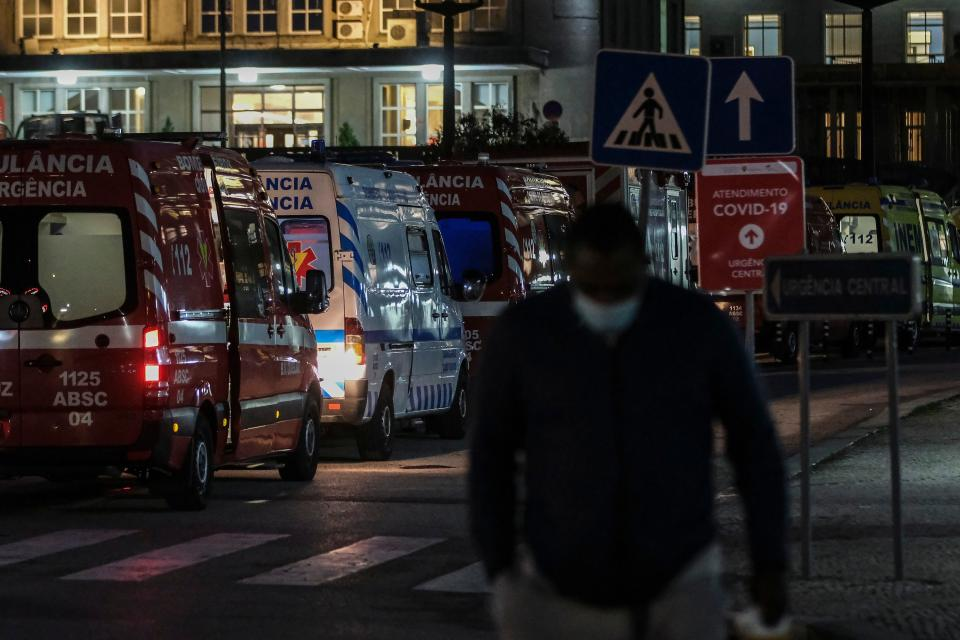 A man walks past ambulances queuing outside the Santa Maria Hospital in Lisbon on January 22, 2021. - Portuguese voters will head to the polls to choose a president in two days, with the dramatic context of a coronavirus lockdown creating more headlines than the expected re-election of incumbent Marcelo Rebelo de Sousa. (Photo by CARLOS COSTA / AFP) (Photo by CARLOS COSTA/AFP via Getty Images)