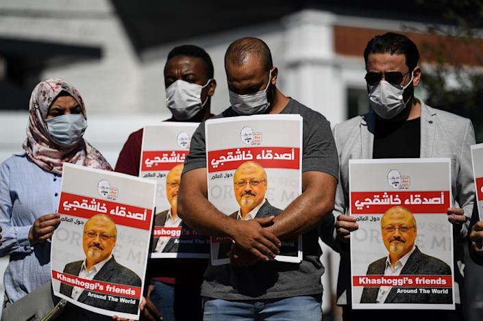 People hold posters bearing Khashoggi's picture at an Oct. 2, 2020, event marking the second-year anniversary of his death. (Photo: OZAN KOSE/AFP via Getty Images)