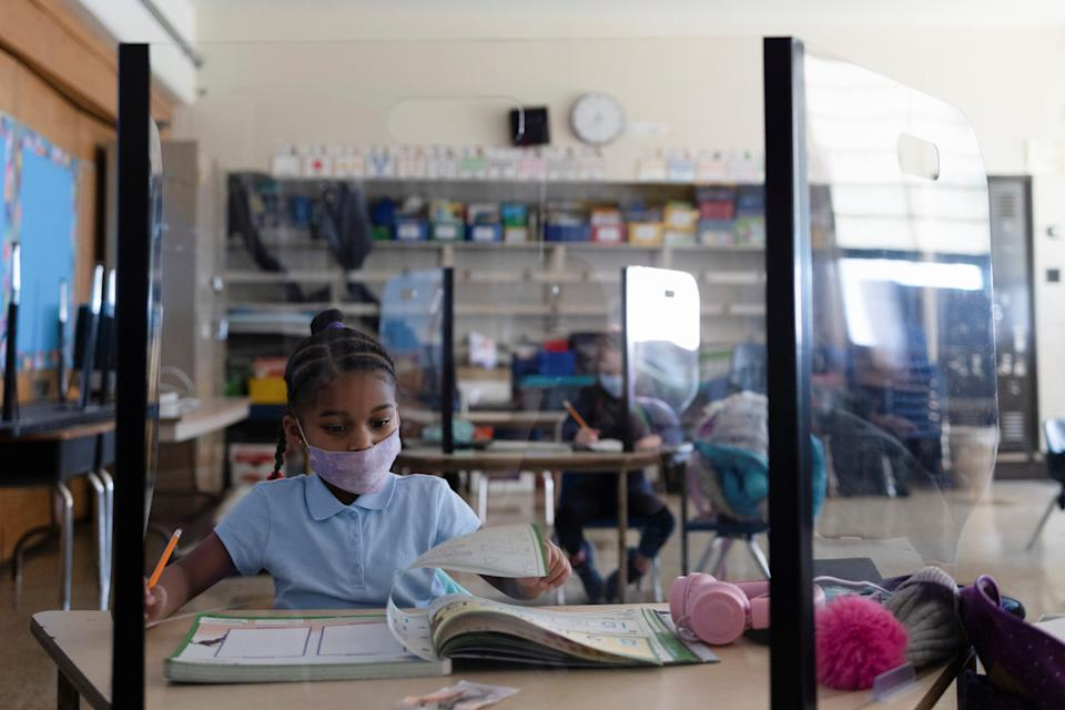 A girl attends school from a booth as students return to school as coronavirus disease (COVID-19) restrictions are lifted in Philadelphia, Pennsylvania on March 8, 2021. (Hannah Beier/Reuters)