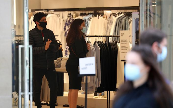 People wearing masks in Buchanan Street after it became compulsory to wear face coverings in shops. - Andrew Milligan/PA