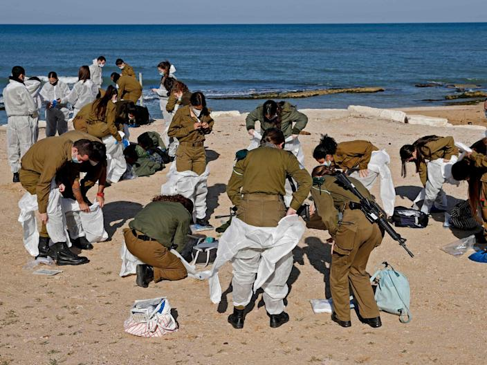 Israeli soldiers arrive to clean up the contaminated Sharon beach national park, north of Tel Aviv city, on February 22 2021 (AFP/Getty)